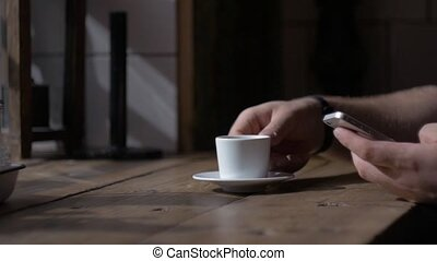 Man sits with smartphone at table with cup of coffee. dark...