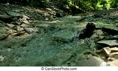 Large stones on a mountain river with clear blue water....