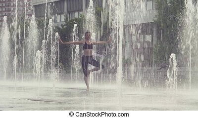 Young woman standing in tree position inside the fountain....