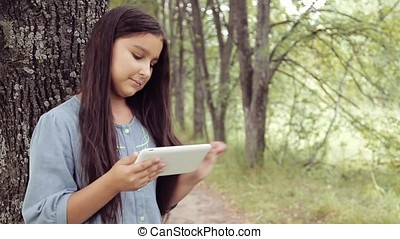 Portrait. A beautiful girl stands by the tree using a tablet and laughs