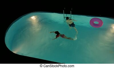 Boy and girl bathe in the pool at night. Children amusement...