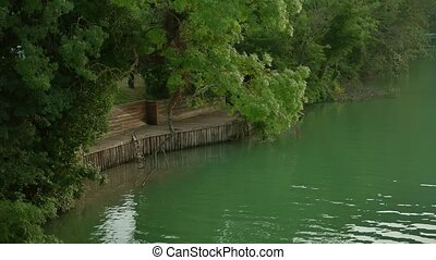 wooden pier next to a river of water and green forest trees....