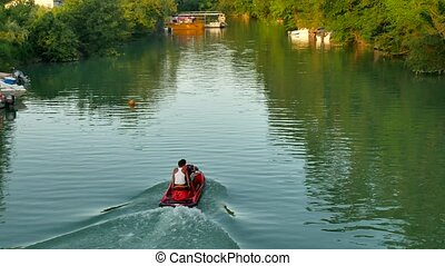 Men ride a hydrocycle on the lake's river nature. - Men ride...