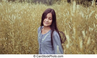 Portrait. A Beautiful little girl is walking on a field in tall grass and smiling with happiness