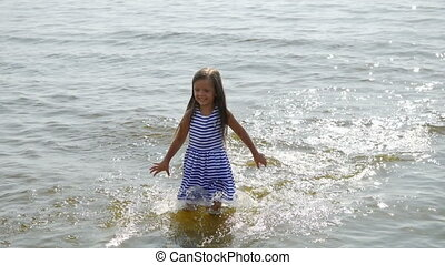 baby girl in a striped dress and runs sea