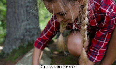 Young woman traveler kindle fire using flint. Starting fire...