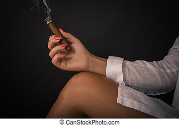 Closeup of woman hand holds tompus cigare on her bare leg....
