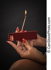 Womens hands ignite big matches for a tompus cigare or a...