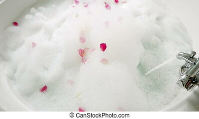 water flows from the tap in a bath with foam