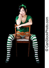 Girl sitting in chair - A young woman dressed in green...