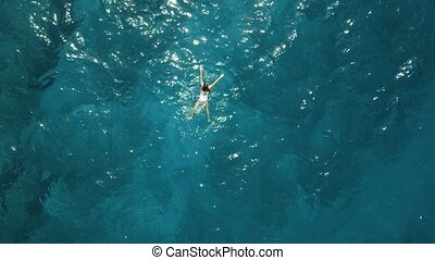 Aerial top down view of a girl in a white swimsuit swimming...