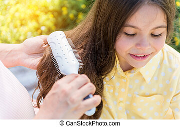 Careful expectant mother combing hair of girl - Close up of...