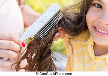 Pregnant woman doing hairstyle for her little daughter -...