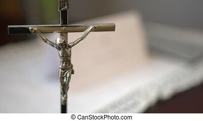 Metal Crucifix with Holy Bible Blurred in Background