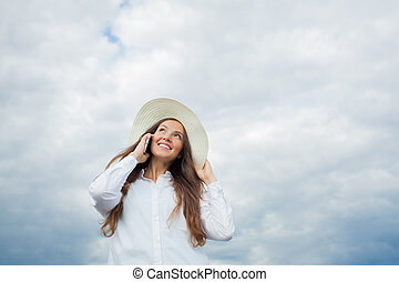 Beautiful smiling girl in a white hat with a wide brim talking on the phone on background of storm clouds