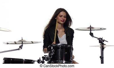 Girl starts playing energetic music, she fun, smiles. White...