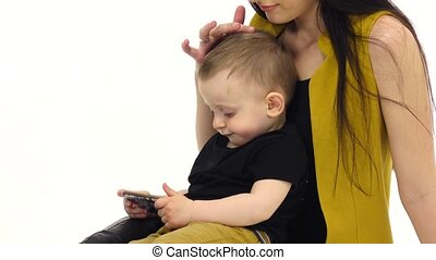 Woman is sitting on the floor with her baby, she is stroking...