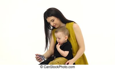 Mother holds her son on her lap and trains him. White...