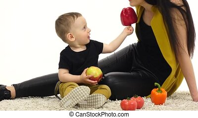 Mom and son are sitting on the floor holding vegetables. White background