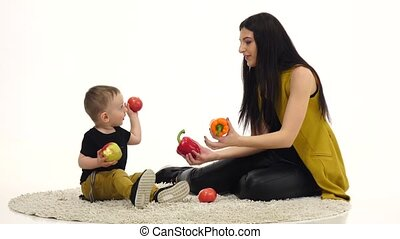 Mom and child are sitting on the floor, around a lot of vegetables and fruits. White background