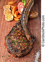 Succulent grilled tomahawk beef steak on the bone with...