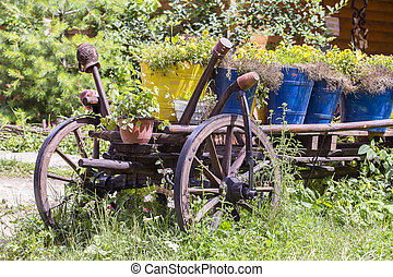Old wheel wooden cart with flowers in the garden....