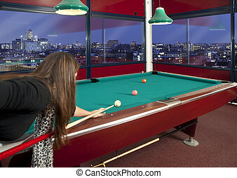Playing pool - Young woman playing pool in a metroplitan...
