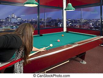 Playing pool - Young woman playing pool in a metroplitan...