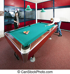 Playing pool - Two people playing pool in a room with a view...