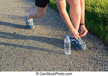 Sport and running idea concept. Young man runner tying shoelaces