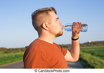 Closeup portrait of young guy drinking water from bottle on...