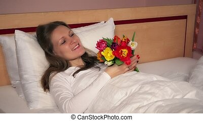Attractive woman girl lying in bed with tulip flowers and looking at camera