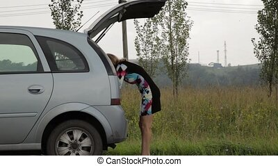 Bewildered Woman opens trunk and takes a tools. Female...