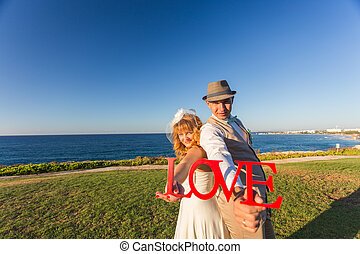 bride and groom with wooden word LOVE in red colour