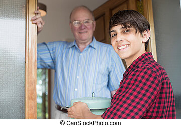 Teenage Boy Bringing Meal For Elderly Male Neighbour