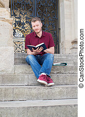 Male University Student Sitting On Steps And Reading Outside Building
