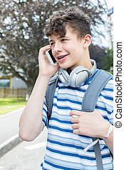 Male Teenage Student Outside College Building Talking On Mobile Phone