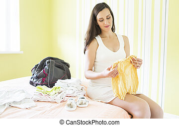 Pregnant woman packing bag for maternity hospital