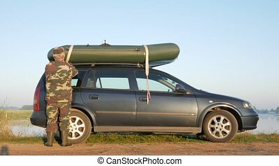 A man loads an inflatable boat onto the roof of the car for transportation. Securely fixes