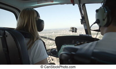 Pilot and passenger in a helicopter - The back of the pilot...