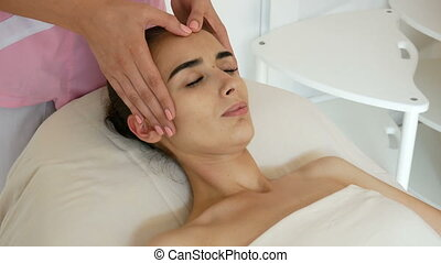 cosmetologist do massage of women's forehead - Young and...