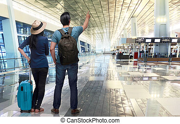 Excited asian couple traveler pointing with hand in the...