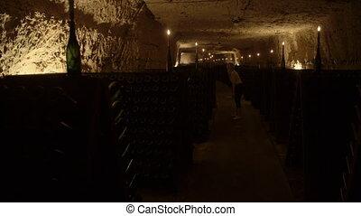 Person exploring around a dark wine cellar - A wide shot of...