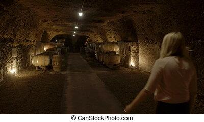 Woman walking into an underground wine cellar - A still wide...