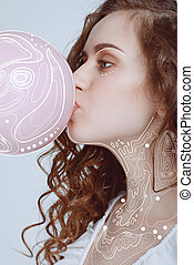 hipster girl blowing bubble gum - side view of young hipster...