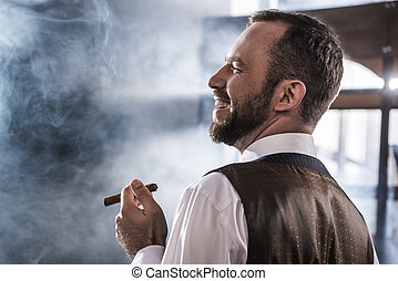 Side view of smiling confident man smoking cigar indoors