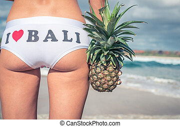 Sexy tropical woman butt close up with exotic pineapple...