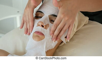 Female cosmetologist making cosmetic facial mask to the female client at the cosmetology centre.