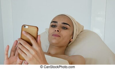 Beautiful women at the cosmetology procedures with phone -...