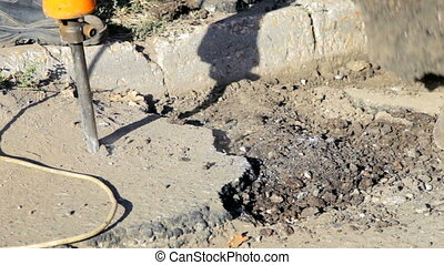 Jackhammer - Road construction worker operates a phneumatic...
